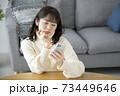 スマートフォンの画面を見ながら頭を抱える若い女性 73449646