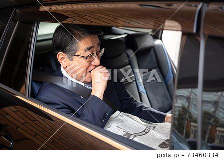 新聞を読むビジネスマン 車内 73460334