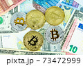 Silver and gold bitcoin coins on paper euro and dollar banknotes. Modern virtual currency 73472999