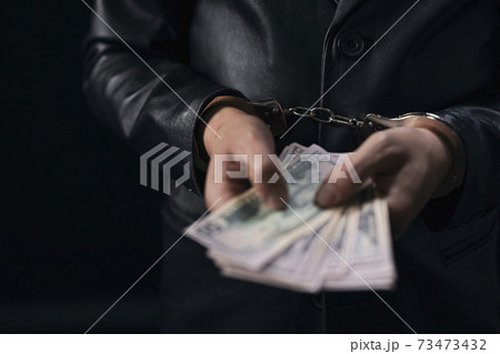 Man in handcuffs holding dollar banknotes 73473432