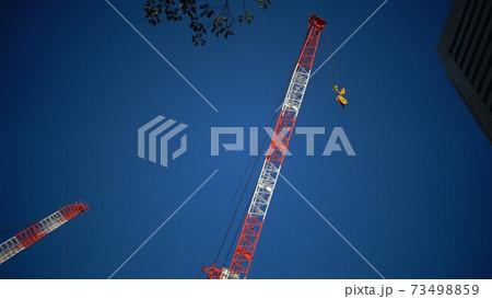 クレーン車と青空と高層ビル建設現場 73498859