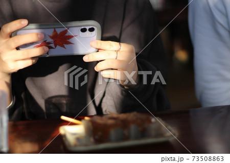 紅葉のIPhoneケーズを持つ女性 73508863