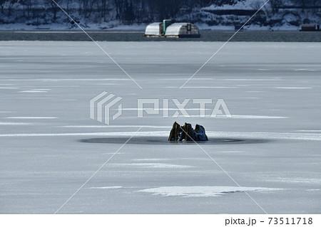 裏磐梯桧原湖・結氷の湖面に雪模様と朽木に釣り小屋船 73511718