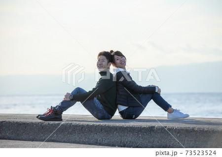 海沿いカップルの体操座り背中合わせ-笑顔 73523524