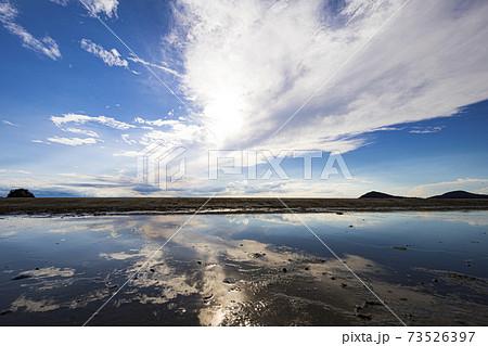 流れる雲と青い空、干潟のリフレクション 73526397