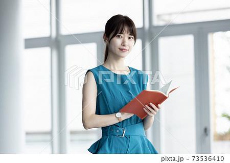手帳を持つ若い女性 73536410
