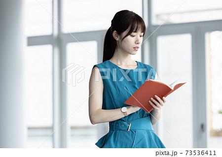 手帳を持つ若い女性 73536411