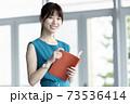 手帳を持つ若い女性 73536414