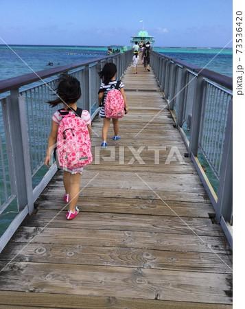 グアムのフィッシュアイに続く桟橋を歩く女の子 73536420