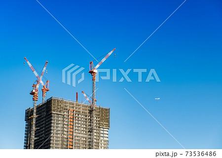 ビル工事中ターワークレーンと飛行機 73536486