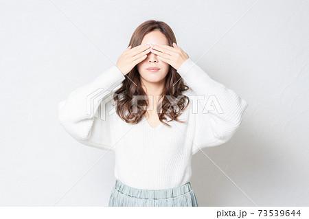 白い壁の前に立って、手で目を隠す若い女性 73539644