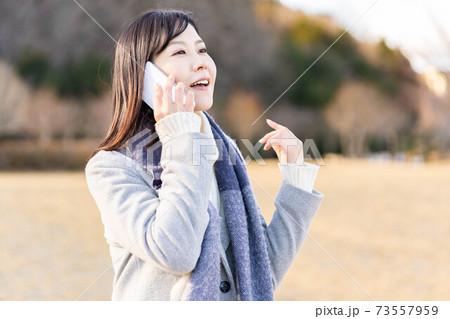 公園の芝生広場でスマホで通話する女性 73557959