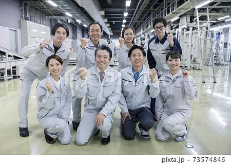 工場内でガッツポーズをする大人数の作業員 73574846