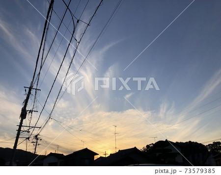 夕方の空に広がる雲と電線と街並み 73579385