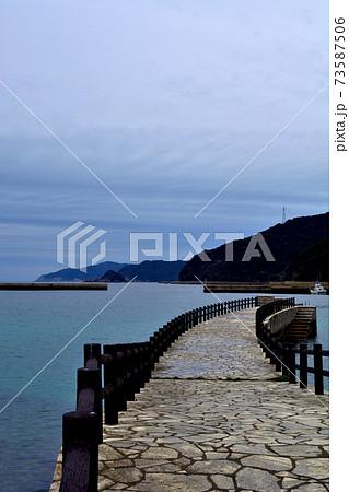 透き通った海と曇り空と長く伸びる堤防 73587506