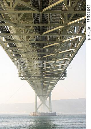 朝の明石海峡大橋を真下から見る。(神戸市側から撮影。写真奥の陸地は淡路島。) 73591846