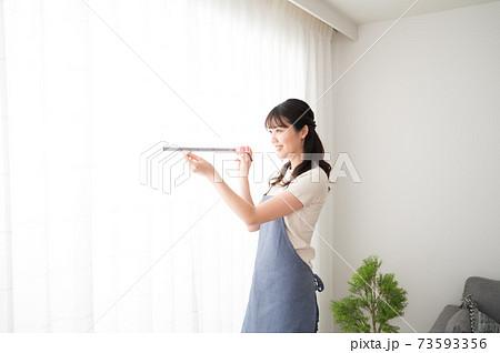 メジャーでカーテンの寸法を測る女性 73593356