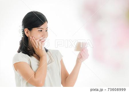 スマホを操作する女性 春のイメージ 73608999