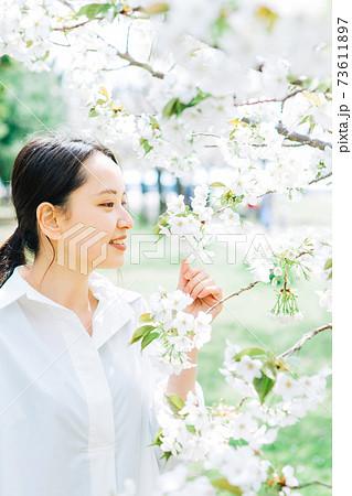 白い桜と若い女性 73611897