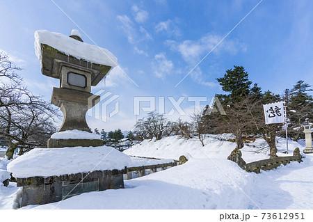 冬の上杉神社 龍の軍旗と石灯篭 山形県米沢市 73612951