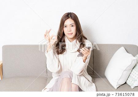 リビングのソファに座って、スマホを操作する若い女性 73615078