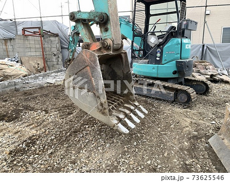 解体現場で仕事をする青緑のショベルカー 73625546