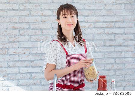 キッチンでパスタ料理を作る若い女性 73635009