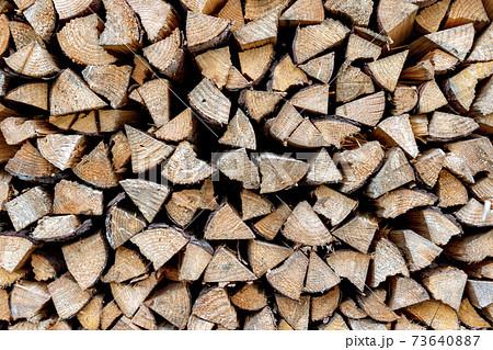 冬支度に民家の庭に積まれた薪の山 73640887