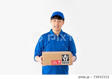 荷物を持つ白背景の笑顔の宅配便の男性 73642523