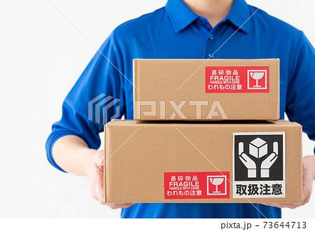 荷物を持つ白背景の宅配便の男性の手元のアップ 73644713