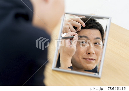 鏡を見ながら眉をかく男性 男性のメイク イメージ 73646116