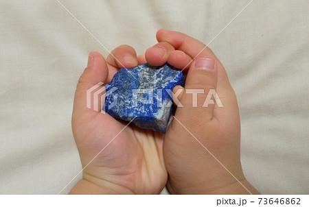 壊れた地球のかけらを大事に持つ子供の手のひら。ラピスラズリ原石 73646862