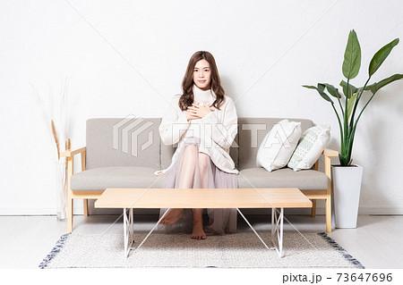 リビングのソファに座って、胸に手を当てる若い女性 73647696