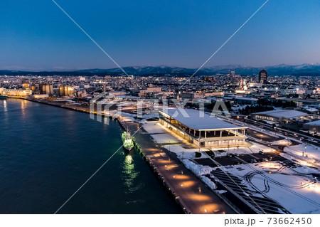 雪化粧、夕暮れの金沢港クルーズターミナルと金沢の街並み 73662450