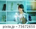オフィスでスマホを操作するカジュアル衣装の若い女性のネットイメージ 73672650
