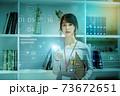 オフィスでスマホを操作するカジュアル衣装の若い女性のネットイメージ 73672651