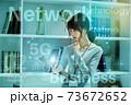 オフィスでスマホを操作するカジュアル衣装の若い女性のネットイメージ 73672652