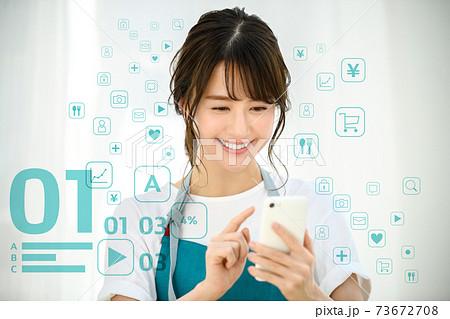 自宅でスマホを操作するエプロン姿の若い主婦のネットイメージ 73672708