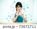 自宅でスマホを操作するエプロン姿の若い主婦のネットイメージ 73672711