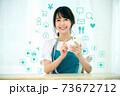 自宅でスマホを操作するエプロン姿の若い主婦のネットイメージ 73672712