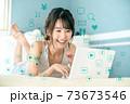 自宅のベッドの上でリラックスしながらパソコンでネットを見る若い女性 73673546