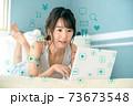 自宅のベッドの上でリラックスしながらパソコンでネットを見る若い女性 73673548