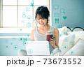 自宅のベッドの上でリラックスしながらパソコンでネットを見る若い女性 73673552