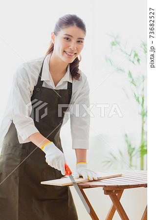 板を切る女性 73682527