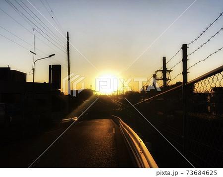 夕暮れの街並みのシルエットと街に沈む夕日のある風景 73684625