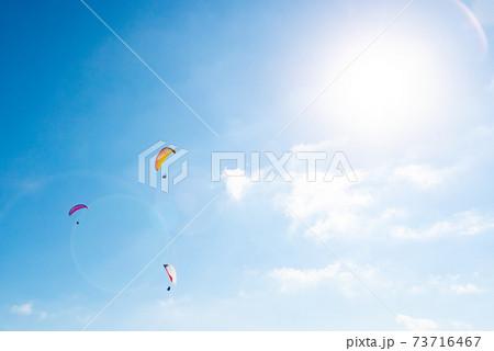 夏の青い空を飛ぶバラグライダーと太陽 73716467