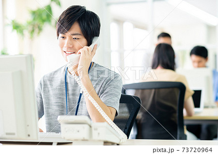 電話するオフィスの若いエンジニア 73720964