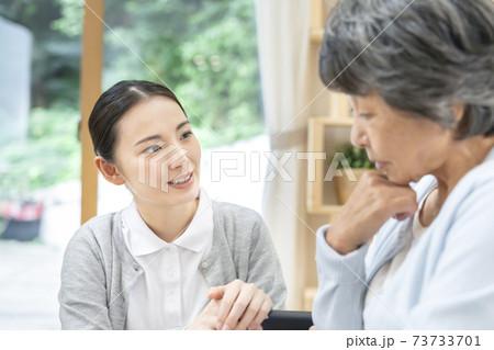 元気の無い利用者と話をする若い女性介護士 73733701