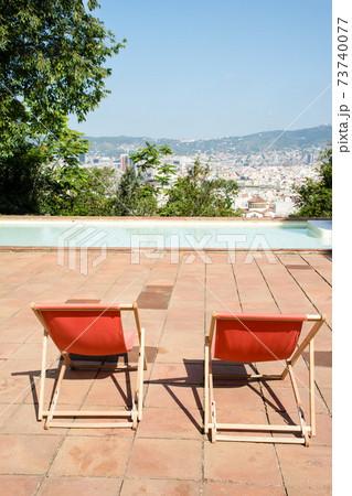 スペインバルセロナの町を見下ろす丘の庭に置かれた布張りの折りたたみ椅子 73740077
