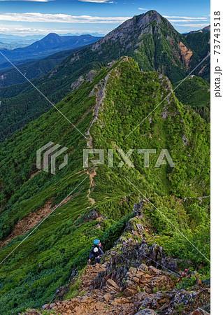 八ヶ岳連峰・権現岳稜線の岩場を行く登山者と阿弥陀岳・蓼科山の眺め 73743518